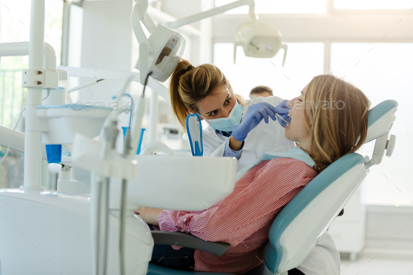 Perfect smile!Female dentist is examining her beautiful patient in dentist's office. - Stock Photo - Images