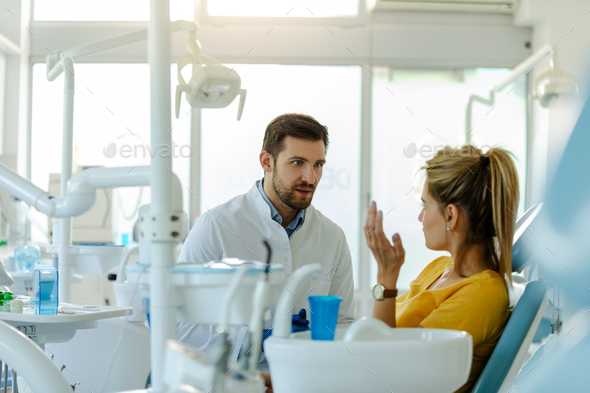 Male dentist in dental office talking with female patient and preparing her for treatment. - Stock Photo - Images