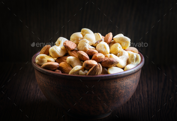 Mix of cashews and almonds in clay plate - Stock Photo - Images