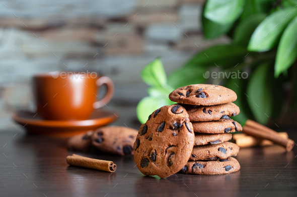 Oatmeal cookies with chocolate on the table against background of cup of coffee and green leaves - Stock Photo - Images