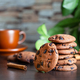 Oatmeal cookies with chocolate on the table against background of cup of coffee and green leaves - PhotoDune Item for Sale