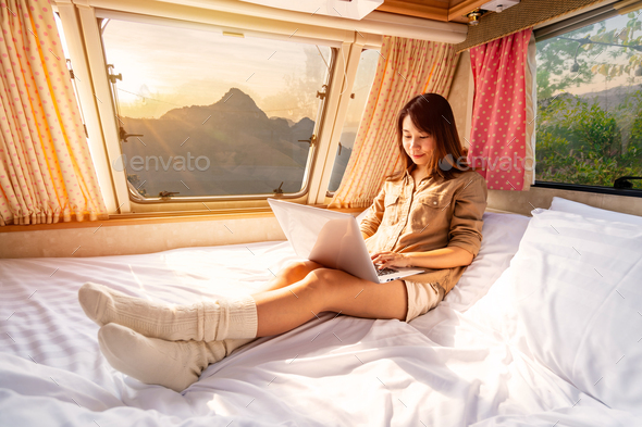 Young woman traveler laying in camper van and using laptop to watch movies and listen to music - Stock Photo - Images