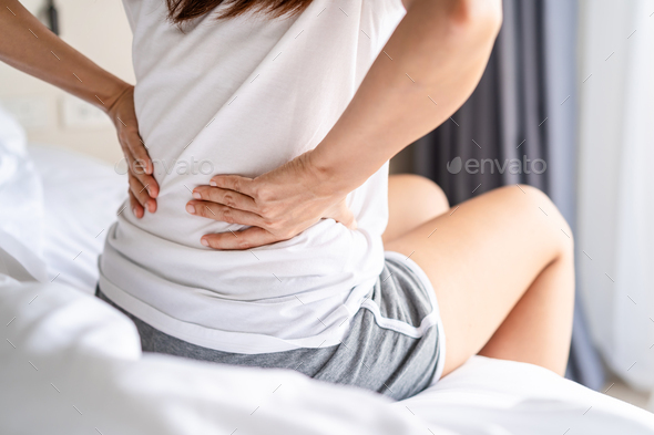 Woman suffering from back ache on the bed, healthcare and problem concept - Stock Photo - Images