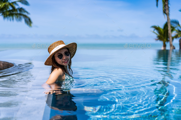 Young woman traveler relaxing and enjoying by a tropical resort pool while traveling - Stock Photo - Images