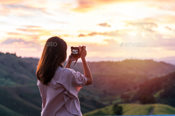 Young woman traveler taking a beautiful sunset over the mountains, Travel lifestyle concept - Stock Photo - Images