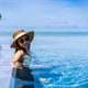 Young woman traveler relaxing and enjoying by a tropical resort pool while traveling - PhotoDune Item for Sale