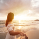 Young woman traveler holding man's hand and looking beautiful sunset on the beach - PhotoDune Item for Sale