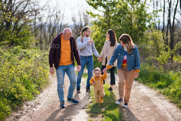 Small toddler with parents and grandparents on a walk outdoors in nature - Stock Photo - Images