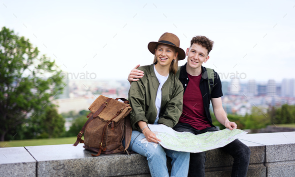 Young couple travelers with map in city on holiday, resting and planning - Stock Photo - Images