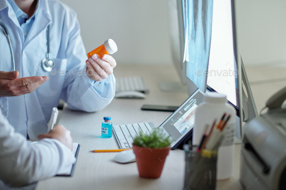 Doctors discussing pills and vaccines - Stock Photo - Images