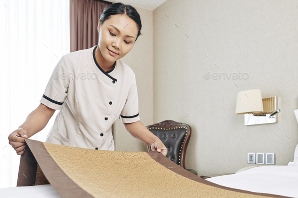 Maid putting decorative runner on bed - Stock Photo - Images