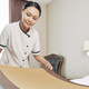 Maid putting decorative runner on bed - PhotoDune Item for Sale