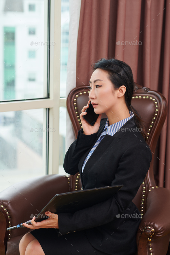 Serious businesswoman talking on phone - Stock Photo - Images