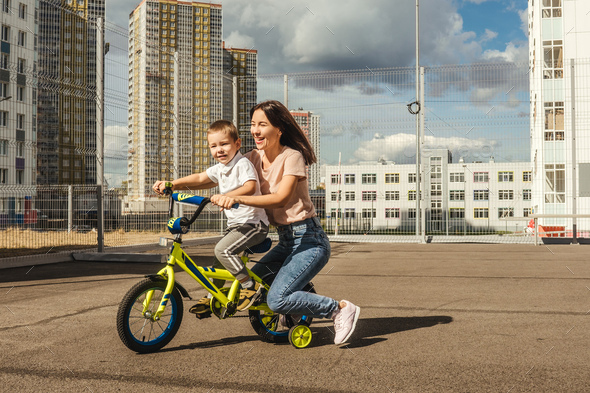 Boy rides a bike with his mother. - Stock Photo - Images