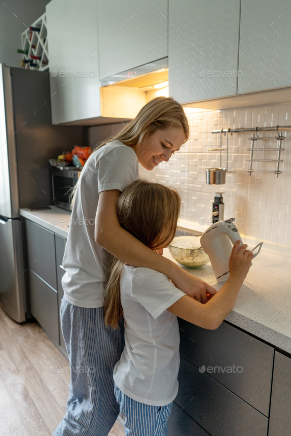 Mother with little daughter cooking at home. - Stock Photo - Images