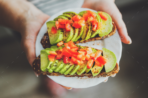 Woman holding plate with avocado toasts - Stock Photo - Images