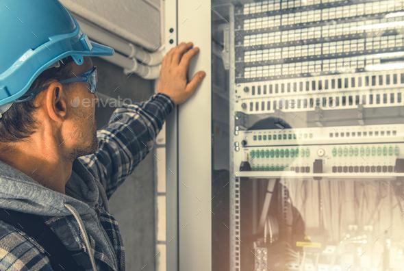 Telecommunication Technician Looking Inside Servers Rack - Stock Photo - Images