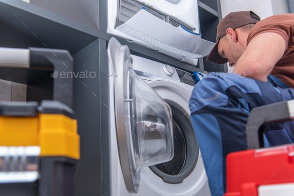 Technician Repairs Broken Washing Machine - Stock Photo - Images