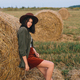 Beautiful stylish woman in hat standing at hay bale in summer evening field. Relaxing in countryside - PhotoDune Item for Sale