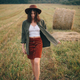 Beautiful stylish woman in hat walking at hay bales in summer evening field. Vacation in countryside - PhotoDune Item for Sale
