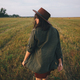 Beautiful carefree woman in hat walking and smiling in evening summer field. Relaxing in countryside - PhotoDune Item for Sale