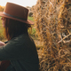 Beautiful stylish woman in hat sitting at haystacks in evening sunset in summer field. Atmospheric - PhotoDune Item for Sale