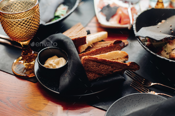 Snack with sauce on black plate with napkin - Stock Photo - Images