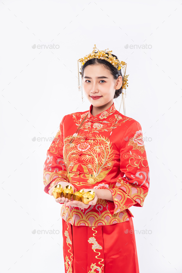 Woman wear Cheongsam suit and crown give gold to her family for lucky in chinese new year - Stock Photo - Images