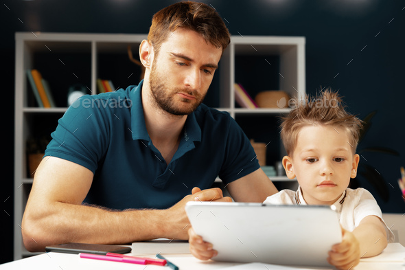 Young boy sitting with his father at the table and using laptop - Stock Photo - Images