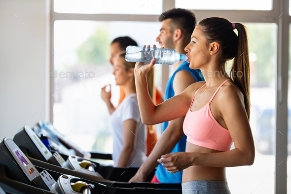 Happy young fit woman drinking during workout, running in the gym - Stock Photo - Images