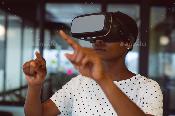 Smiling african american woman using vr headset at work - Stock Photo - Images