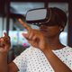 Smiling african american woman using vr headset at work - PhotoDune Item for Sale