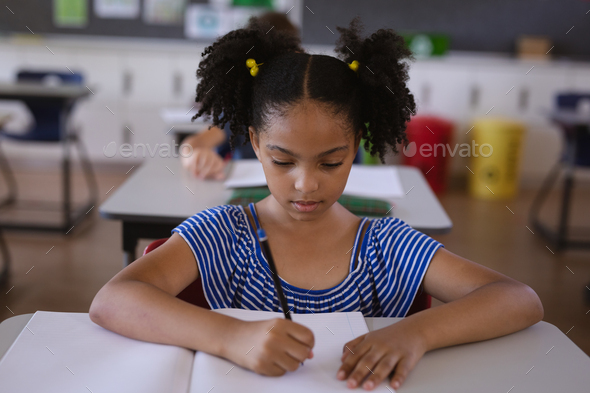 African american girl studying while sitting on her desk in the class at school - Stock Photo - Images