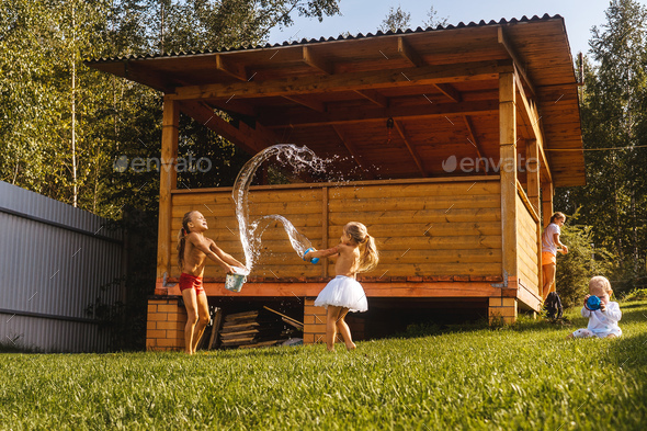 Happy kids playing with water in garden - Stock Photo - Images