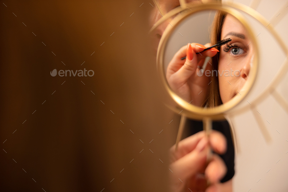 Woman Holding Mirror While Female Cosmetologist Using Mascara - Stock Photo - Images