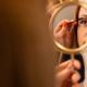 Woman Holding Mirror While Female Cosmetologist Using Mascara - PhotoDune Item for Sale
