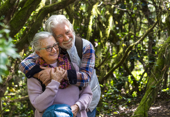 A senior couple tenderly embraced enjoying mountain hike in the woods among trunks and branches - Stock Photo - Images