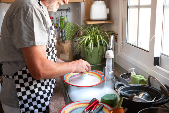 Senior man with white beard concentrated while washing dishes at home wearing apron. Bright light - Stock Photo - Images