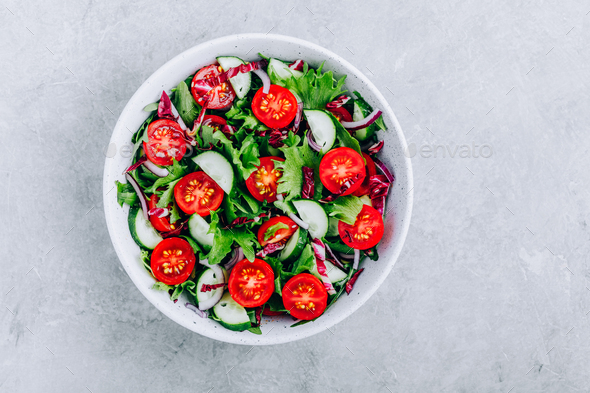 Green salad bowl with tomatoes, cucumbers, red onions, radicchio and fresh lettuce. - Stock Photo - Images