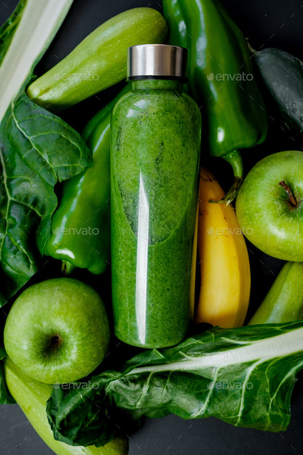 Close up Green vegetables and smoothies in a plastic bottle on black background - Stock Photo - Images