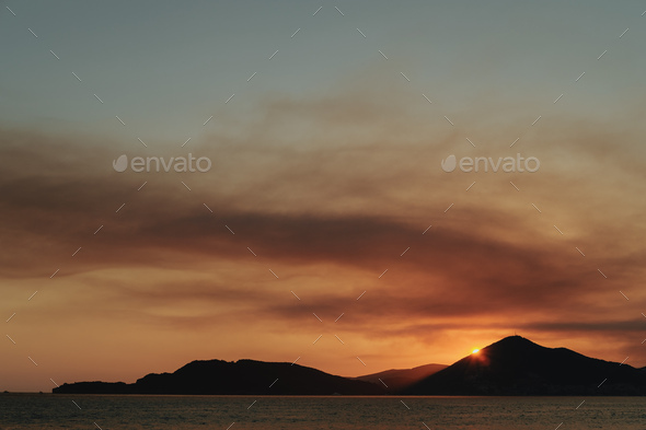 Orange sunset at the sea with mountains silhouettes, Montenegro - Stock Photo - Images