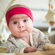Portrait of adorable baby with funny expression on the floor indoors - PhotoDune Item for Sale