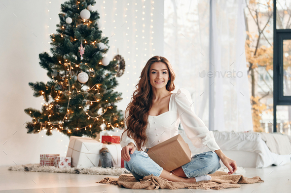 Happy young woman sits indoors near christmas tree and celebrates New year - Stock Photo - Images