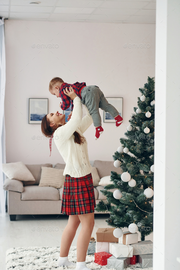 Beautiful young mother holds her little son by hands at home near New year christmas tree - Stock Photo - Images