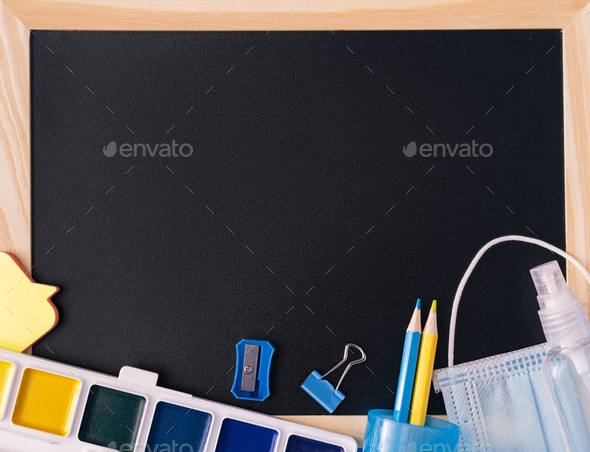 Black school board with school supplies, medical mask and antiseptic - Stock Photo - Images