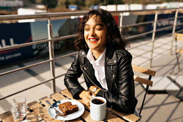 Exited laughing woman with short hair and red lips drinking coffee in good warm day - Stock Photo - Images