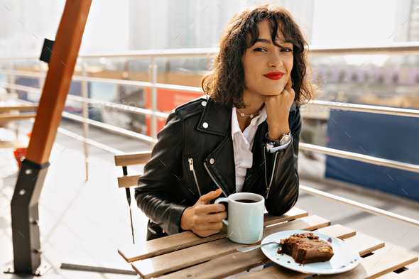 Dreamy lovable girl with short curly hair with red lips sitting on outside terrace - Stock Photo - Images