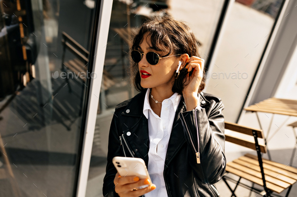 Trendy girl with red lips wearing leather jacket and black glasses listening music - Stock Photo - Images