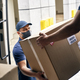 Close up of couriers unloading packages from a delivery truck - PhotoDune Item for Sale