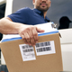 Close up of courier holding cardboard box for delivery - PhotoDune Item for Sale